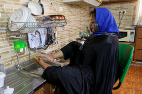 Sheyda Shokravi, a professional painter who was born with no arms, washes the dishes with her feet, December 3, 2018.