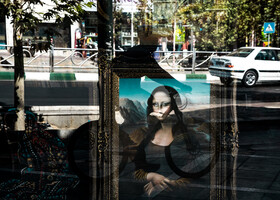 The Pictorial carpets in Valiasr Street and the reflection of a cyclist crossing the sidewalk are seen in the photo, Tehran, Iran, October 9, 2019.