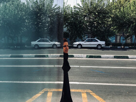 The reflection of a woman is seen in a bus stop shelter in Vesal Street, Tehra, Iran, October 13, 2019.