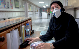 """Ms. Beiranvand, the secretary of Kamkar Hospital is seen in the photo, Qom, Iran, March 12, 2020. When asked about the current situation in fighting the coronavirus, she said, """"Despite having diabetes, I continue working at the hospital""""."""