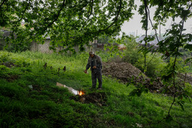 A man burns the coffin of a coronavirus case after the burial ceremony, Mazandaran, Iran, May 3, 2020.