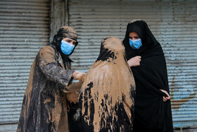 Two women apply a mixture of clay and water on their clothes as a sign of mourning for the martyrdom anniversary of Imam Hussain (peace be upon him), Lorestan, Iran, August 30, 2020.