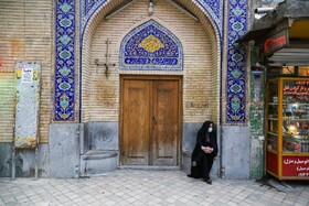 A woman sits next to the door of a mosque in Isfahan, Iran, March 15, 2020.