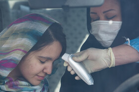 The temperature of passengers is taken in order to recognize the suspicious cases of the coronavirus, Qazvin, Iran, March 11, 2020.